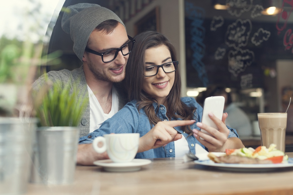 Image of a couple using a mobile device at a cafe