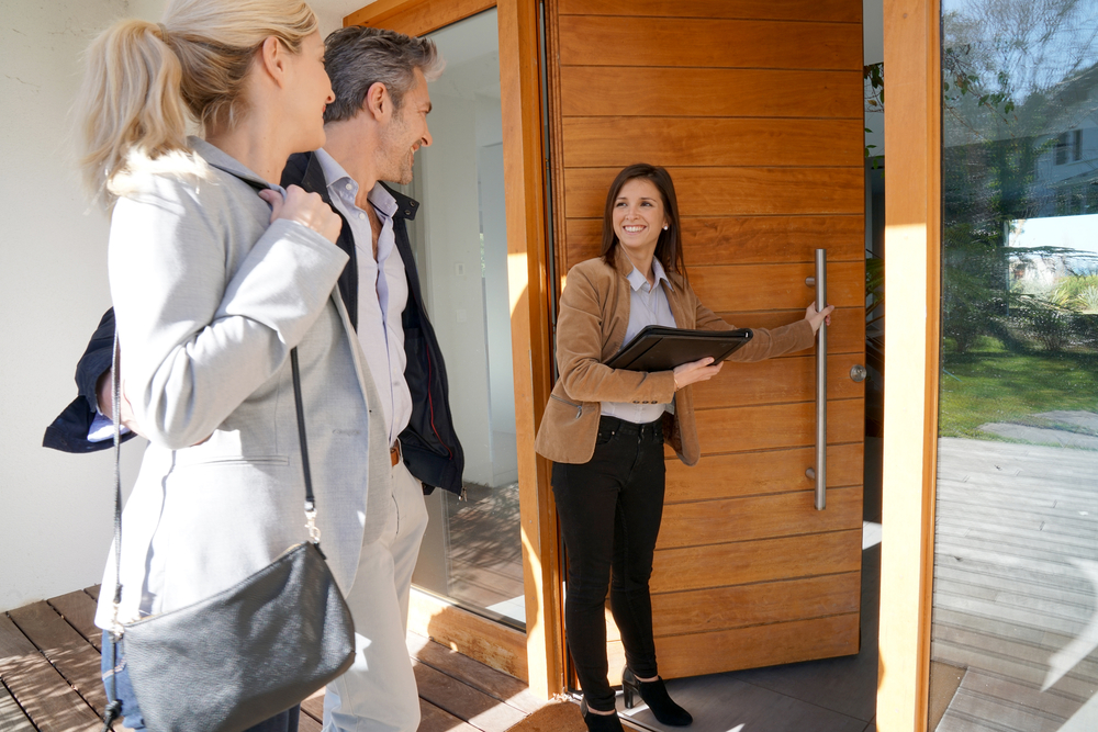 Agent inviting couple into home
